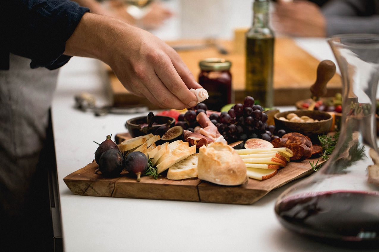 a hand reaching for a charcuterie board on a counter