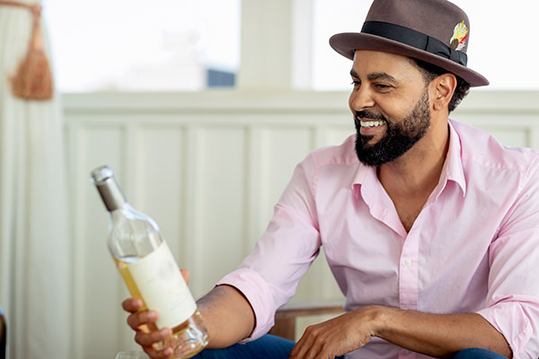 man in hat with white wine in hand