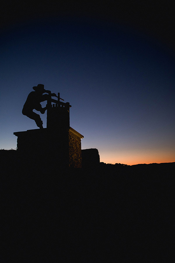 large statue of wine press worker silhouetted against sky and hills at dusk