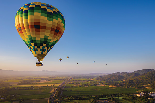 hot air balloons float over Napa Valley