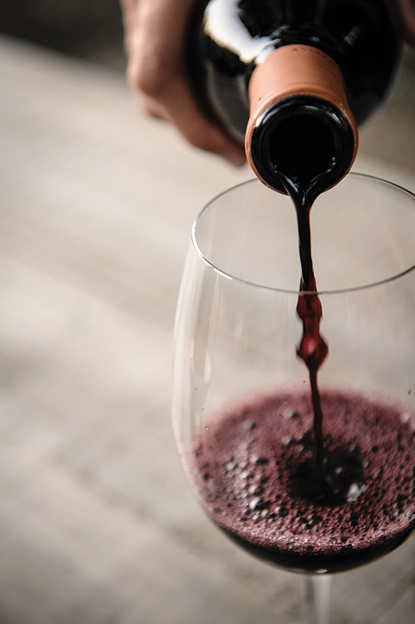 red wine pouring from a bottle into a wine glass