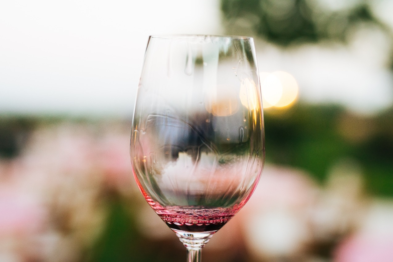 wine glass with a splash of red wine in front of unfocused roses