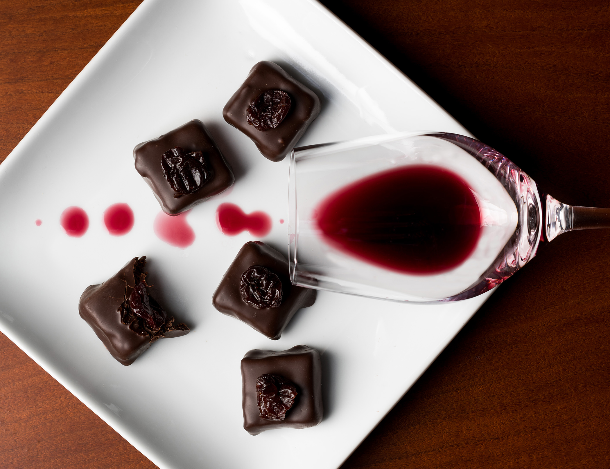red wine in a glass dribbling over a plate with chocolate truffles