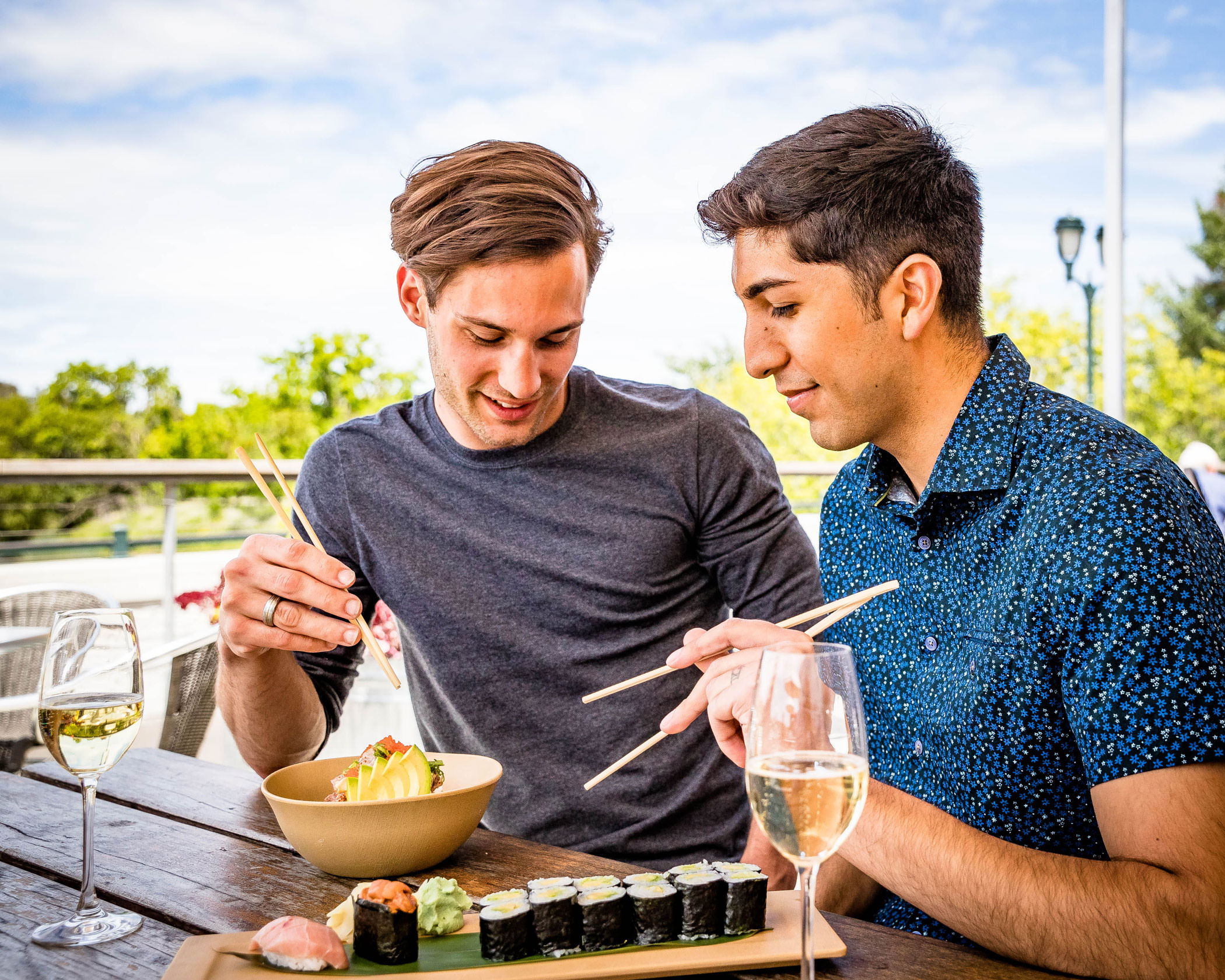 two men sitting outside eat sushi paired with white wine