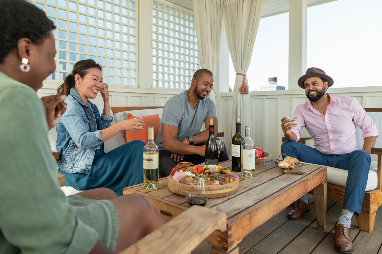 group of four friends laughing and drinking wine on an outdoor porch