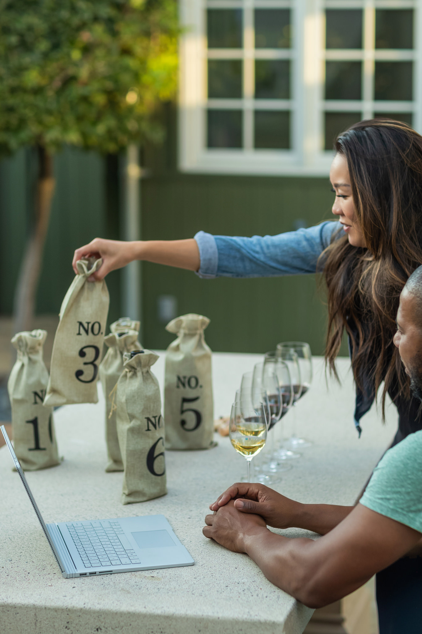 couple at a table with numbered bottles of wine and several tasting glasses lined up